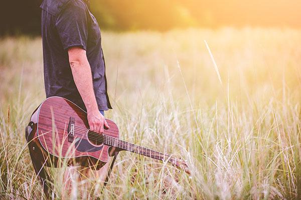 Mann mit Gitarre in hohem Gras